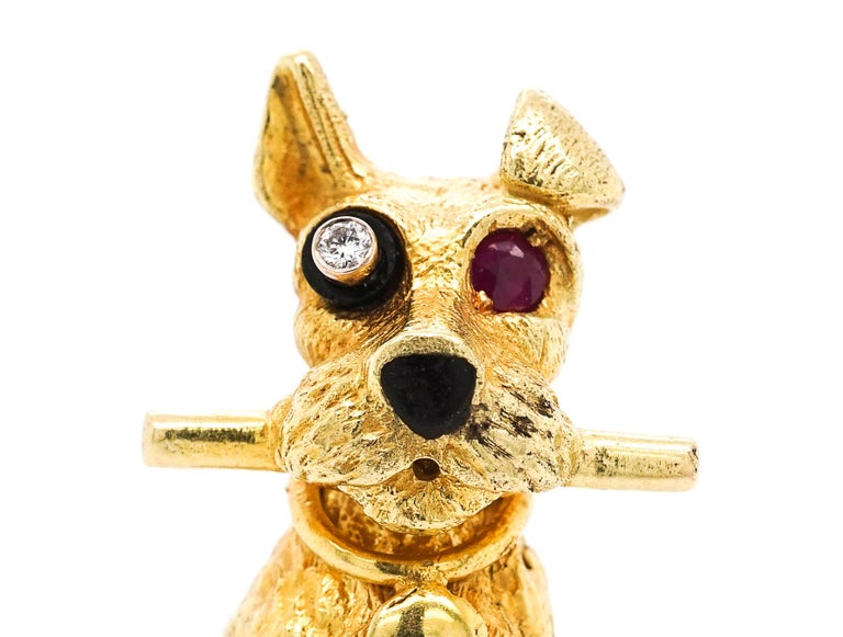 This beautiful 18KT furry terrier clenching a polished stick, with one round diamond eye within a black enamel cylinder, one round ruby eye and black enamel nose, signed Cartier, Paris, no 73, with maker mark.