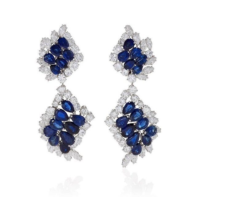 The flowing design of these Cartier sapphire and diamond earrings frames the face with a radiant energy. A tessellation of blue sapphires bounded by dazzling colorless diamonds set in platinum creates a sense of expanding fluidity and movement. The