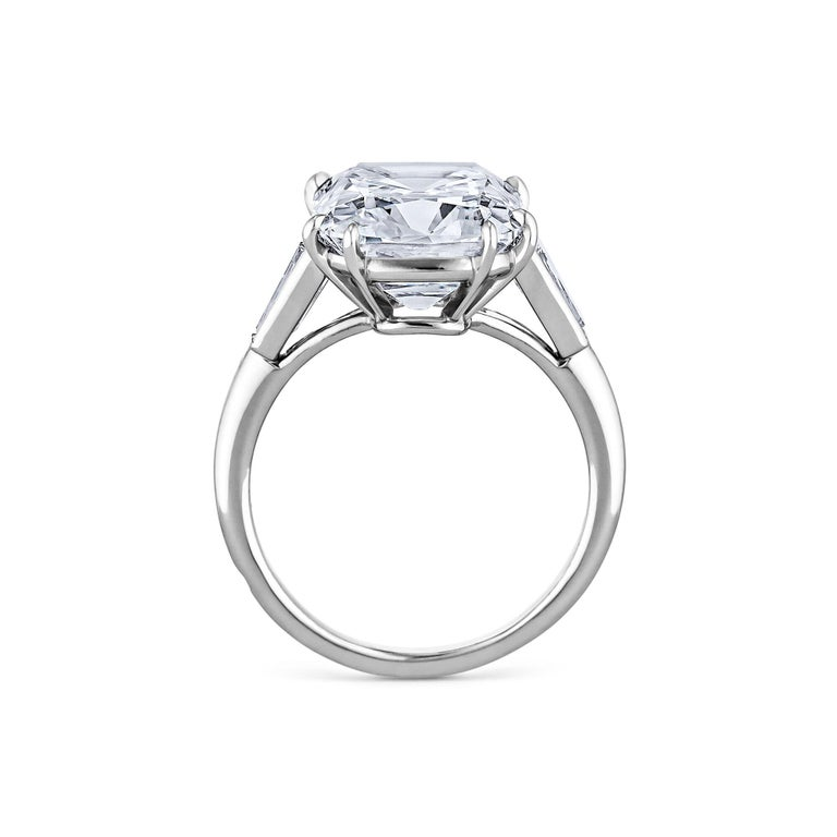 Exuding romance, inner fire, and endless elegance this Cartier Paris Art Deco 7.17 carat cushion cut diamond platinum engagement ring is extraordinary.  Set with two tapered baguettes in a handmade mounting, this timeless jewel is unmatched.  Center