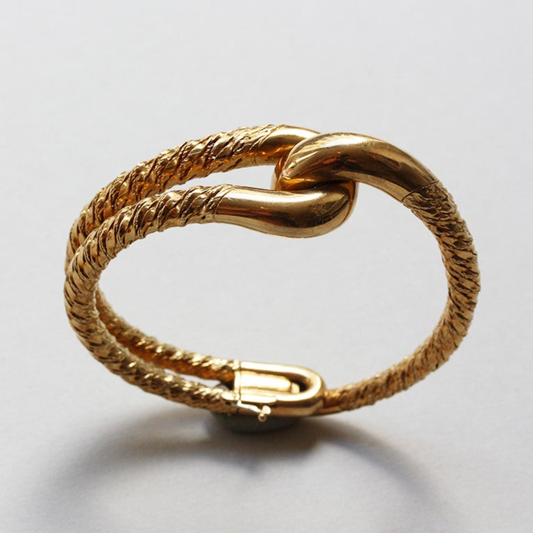 An important 18-carat gold knot bangle, signed and numbered: Cartier Paris, 016 053 by Georges Lenfant. And an 18-carat gold knot pinky ring of twisted thick gold wire. Signed and numbered: Cartier Paris, 36971. Both circa 1970, in their original