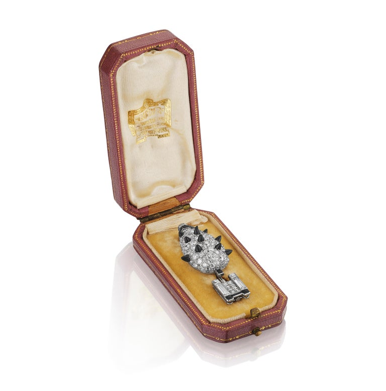 A brooch designed as a potted topiary set throughout with European-cut diamonds, interspersed with French-, baguette-, and single-cut diamonds, accented with black onyx detailing, completed with black enamel accents and a reverse-set diamond at the