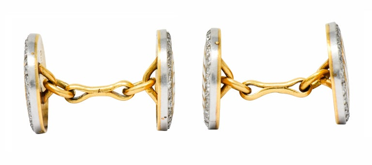 Link style cufflinks with circular disks at each end  Featuring a striped design of white enamel alternating with engraved gold; exhibiting minimal loss  Surrounded by a halo of single cut diamonds weighing in total approximately 1.25 carats; G to J