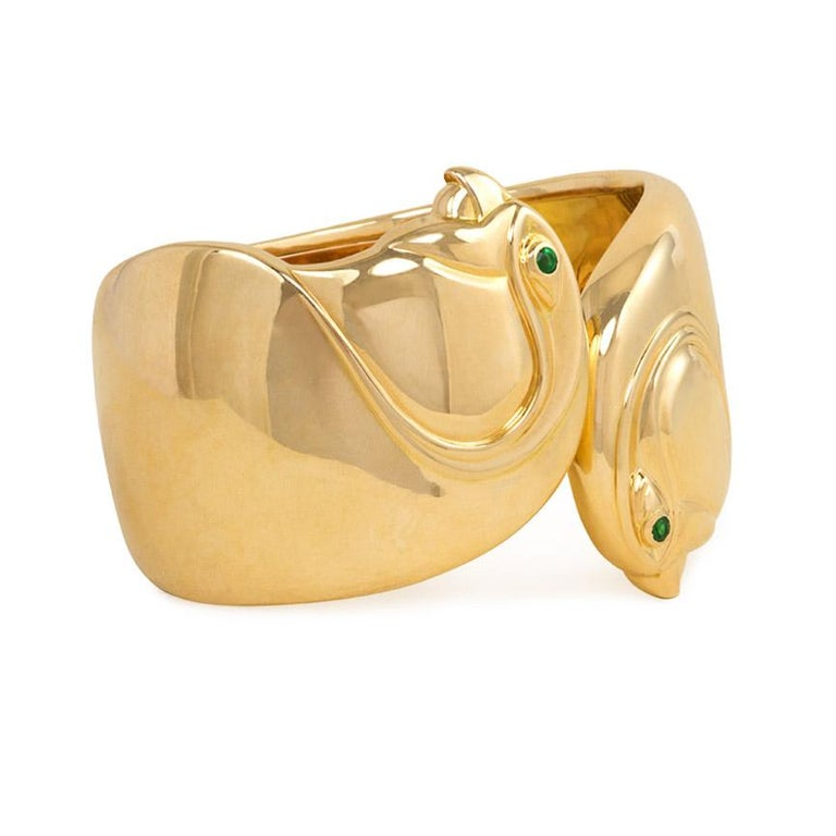 A gold hinged cuff bracelet in the form of a pair of opposed birds' heads with emerald eyes, in 18k.  Cartier, Paris  #619843. Dimensions: 6 3/4