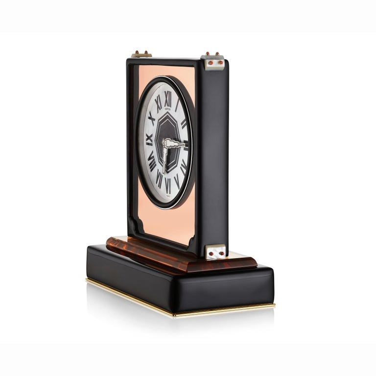 A desk clock composed of a circular mother-of-pearl dial with black enamel Roman numerals set into a rose mirrored rectangular case with black enamel frame, the corners decorated with mother of pearl and coral beads, on a rock crystal and enamel