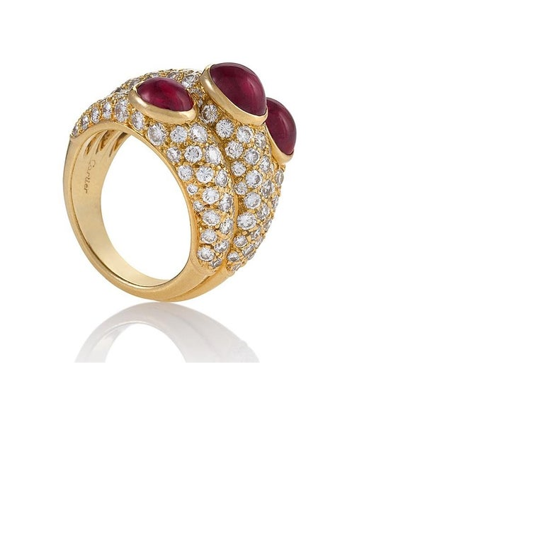A French 18 karat gold ring with diamonds and rubies by Cartier. The ring is comprised of three interlocking diamond-encrusted raised boule-shaped gold bands, each of which feature an oblong cabochon ruby of superb color measuring approximately 4.00