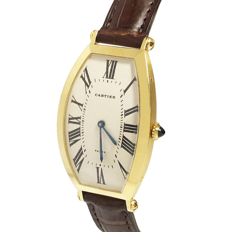 Circa late 1980 Cartier Paris Tonneau Wrist Watch, 46 X 26 Curved and Convex 18K Yellow Gold 2 Piece case. 17 Jewel Mechanical, Manual wind Movement, Sapphire Crown, Engine Turned Silver Dial with White Finish and Black Roman NUmerals. Cartier Brown