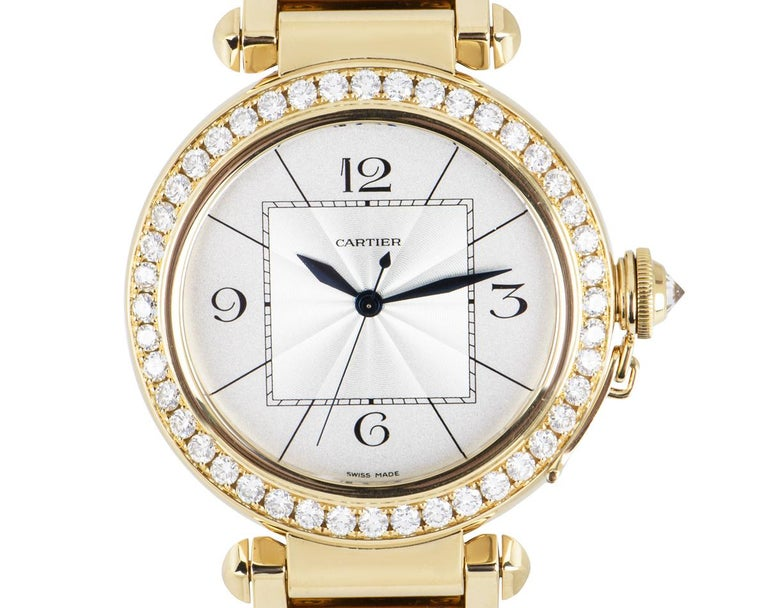 A 42mm Pasha in yellow gold by Cartier, featuring a silver dial with a guilloche centre and sword-shaped hands in blued steel. The bezel is set with 42 round brilliant cut diamonds and the crown, protected by a screw-down cover set with a single
