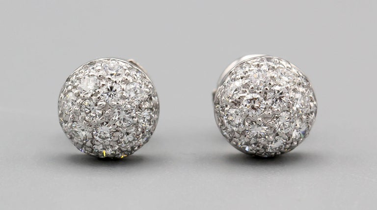 Fine pair of pave diamond and 18k white gold dome earrings by Cartier.  Designed as a stud earring, they are easy to wear day or night, business or casual attire.  Hallmarks: Cartier 750, reference numbers.