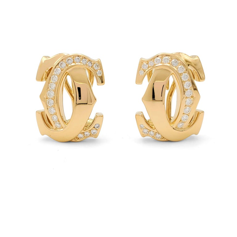 Authentic Cartier 'Penelope' earrings crafted in 18 karat yellow gold center on the iconic interlocking Cartier double-C motif. The earrings are set with an estimated 0.55 carats total weight of round brilliant cut diamonds (E-F color, VS clarity).