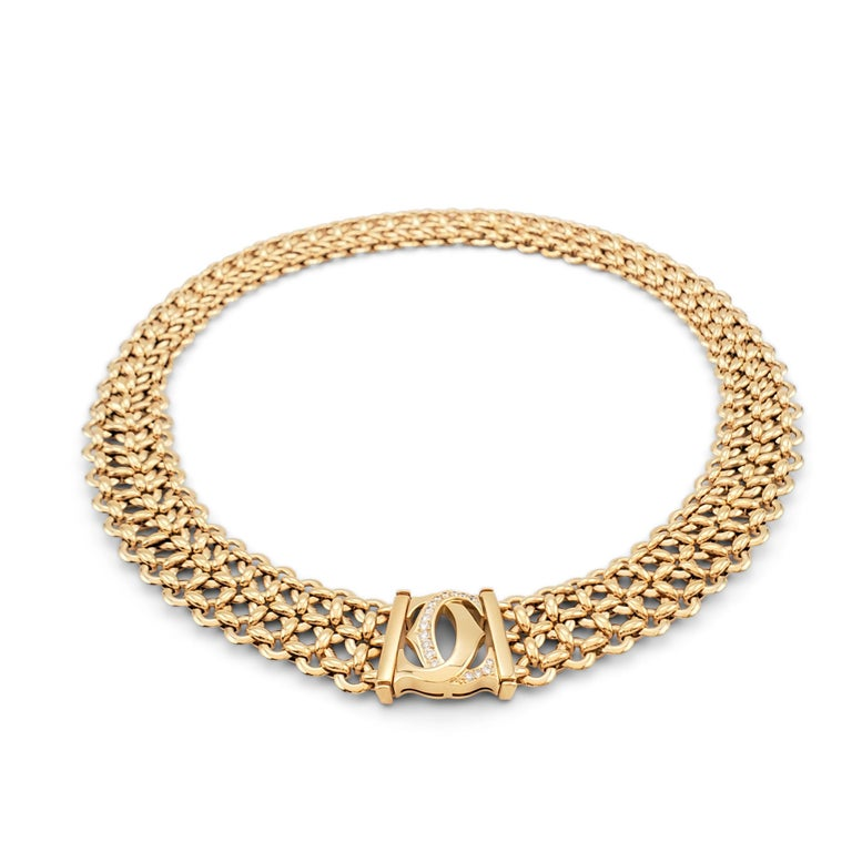 Authentic Cartier 'Penelope' necklace comprised of three-rows of 18 karat yellow gold links centering on the Cartier double-C motif which is set with an estimated 0.30 carats of round brilliant cut diamonds (E-F color, VS clarity). Signed Cartier,
