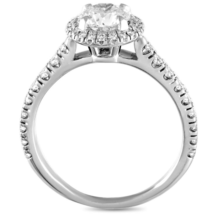 This Cartier engagement ring is crafted from platinum and weighs 4.3 grams. It boasts band thickness of 2 mm and top height of 6 mm, while top dimensions measure 20 by 9 mm. The ring is set with a total of 1.18 carats of diamonds, with the center