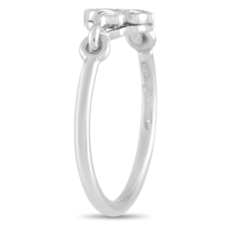 This Cartier Platinum Diamond Ring is a fun twist on a classic diamond ring. The ring is made with Platinum and is set with four round-cut diamonds in a pretty motif. The diamond motif is connected to the rest of the band with interlocking platinum