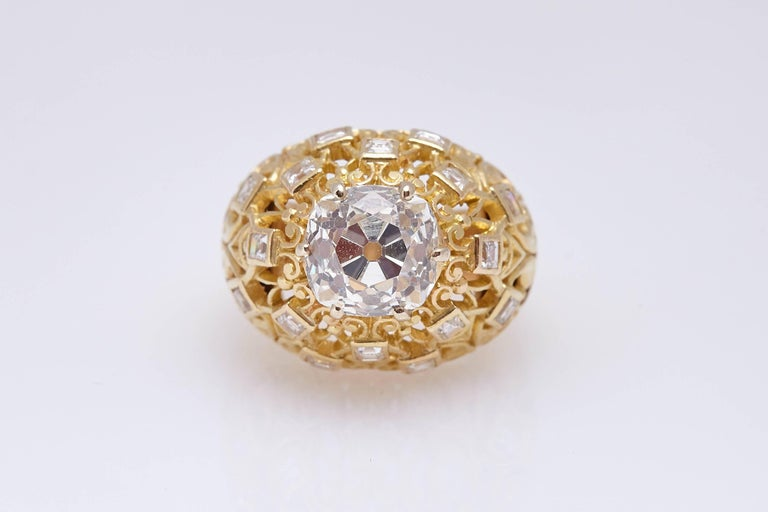 A Cartier retro dome shaped ring in 18kt yellow gold, the mounting embellished with fine round cut diamonds, showcasing an Old Mine Brilliant Cut Diamond weighing 4.24 (L Color, SI1 Clarity - GIA Certificate). Made in France, circa 1950s.