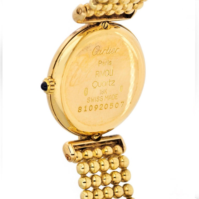 Cartier Rivoli 18K Yellow Gold 1292 Diamonds And Ruby Ladies Watch. The Rivoli was added to Cartier's lineup in the 1990s. It features strong branding with the classic Roman numeral dial, hinged lugs reminiscent of the 1930s and a bracelet made of