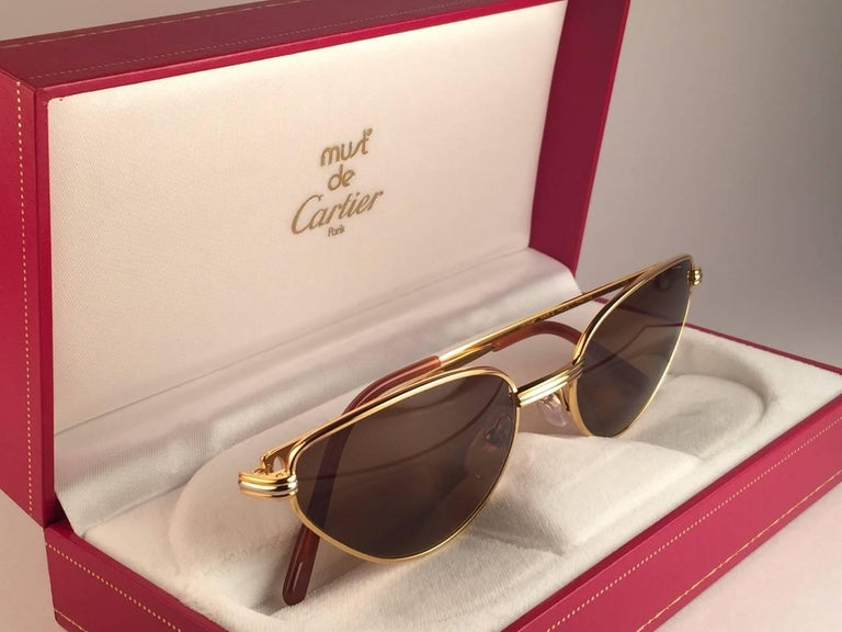 New 1988 Cartier Rivoli Vendome Cat Eye Sunglasses with new honey brown  (uv protection) lenses. The cat's eye frame is with the front and sides in yellow and white gold. All hallmarks. Red enamel ear paddles. Both arms sport the C from Cartier on