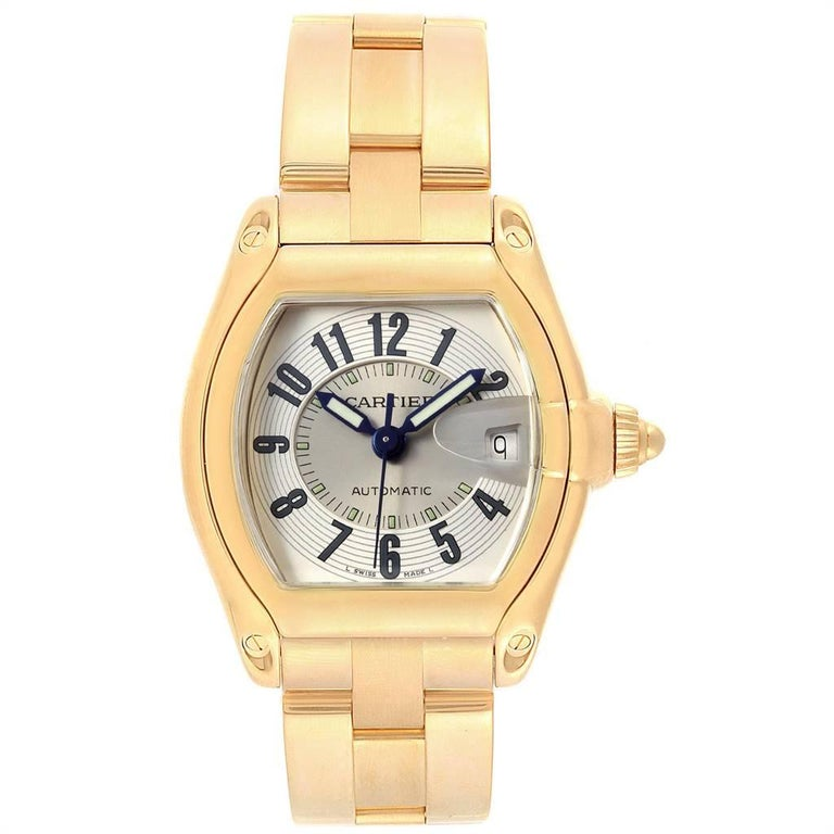 Cartier Roadster 18K Yellow Gold Large Mens Watch W62005V1. Automatic self-winding movement. 18K yellow gold tonneau shaped case 37 x 44 mm. Scratch resistant sapphire crystal with cyclops magnifying glass. Silver sunray effect dial with black