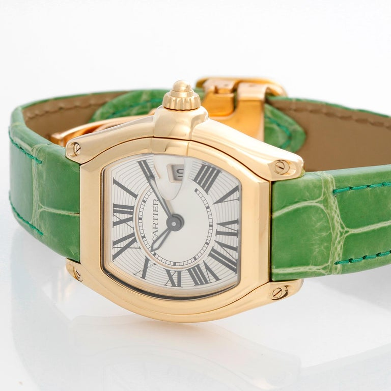 Cartier Roadster 18k Yellow Gold Quartz W62018V1 - Quartz. 18k yellow gold tonneau style case (31mm x 37mm). Silver guilloche dial with black Roman numerals; date at 3 o'clock. Green Cartier Leather Strap with 18K Yellow Gold Deployant Clasp .