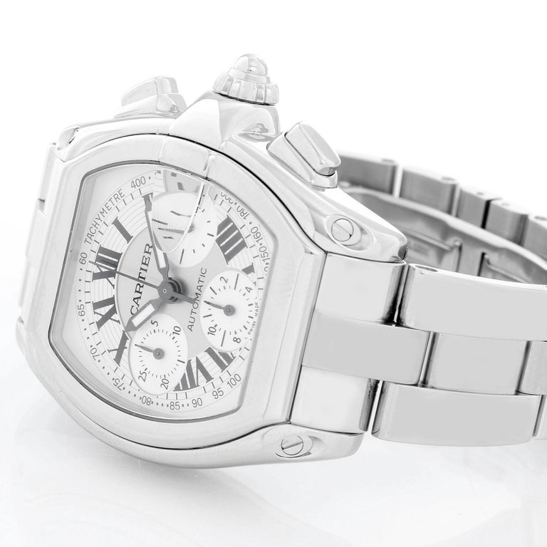 Cartier Roadster Chronograph Stainless Steel Men's Watch - Automatic winding chronograph with date. Stainless steel case (43mm x 48mm). Silver dial with white Roman numerals; date at 3 o'clock. Stainless steel Cartier bracelet with deployant clasp.