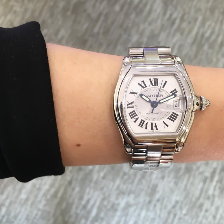 Pre-owned Genuine Cartier Large Roadster Automatic Watch in Stainless Steel. This watch has a silver dial, black roman numerals, luminous sword-shaped hands and a magnified date display. Watch is on a stainless steel brushed and polished link
