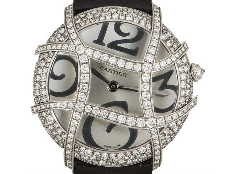 From Cartier, this 37 mm Ronde Folle Libre in white gold features a silver dial concealed by sapphire crystal. The dial is adorned with a curved white gold grid which is set with round brilliant cut diamonds, as is the bezel. A single round