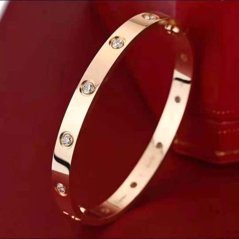 An iconic 18k rose gold full diamond Love bracelet by Cartier. The bracelet is set with 10 round brilliant cut diamonds circulating the outer edge throughout totalling 0.96ct. The bracelet is a size 16 and features the new style screw fitting and