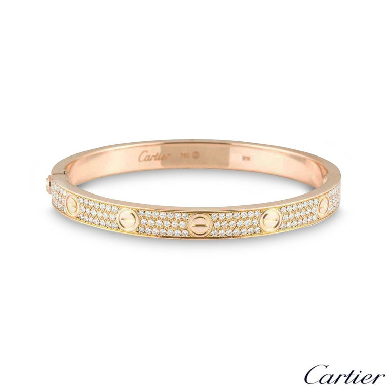 A sparkly 18k rose gold diamond Cartier bracelet from the Love collection. The bracelet comprises of the iconic screw motif on the outer edge complemented with 204 round brilliant cut diamonds throughout, in a pave setting. The diamonds have a total