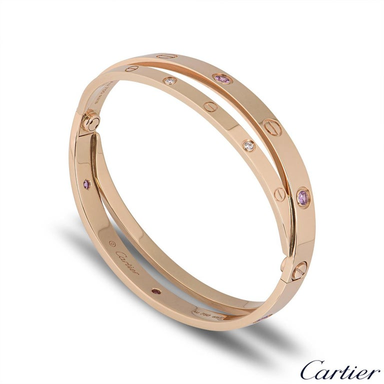 An unworn iconic 18k rose gold half diamond and pink sapphire double Cartier bracelet from the Love collection. The double bangle features the iconic screw motif alternating with 6 round brilliant cut diamonds and 6 pink sapphires displayed around
