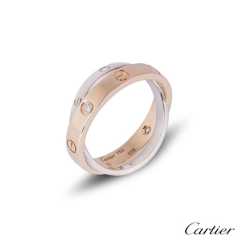 A stylish 18k white and rose gold Cartier double ring from the Love collection. The predominant rose gold ring is set with 6 round brilliant cut diamonds and alternating screw motifs. Interlinking is an 18k white gold band on either side also
