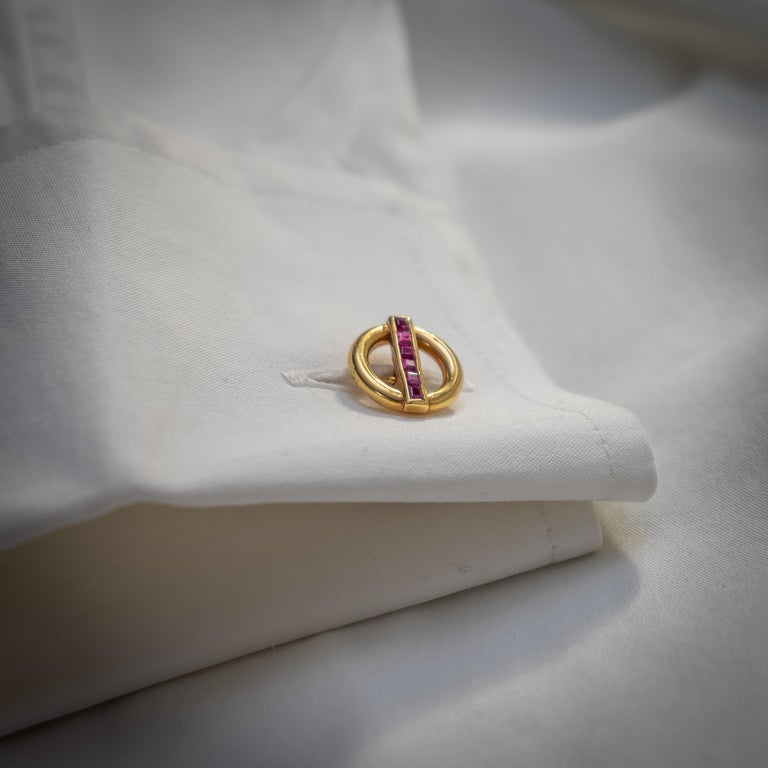 A pair of vintage, Cartier, gold and ruby cufflinks. Each of the double links comprise an open circle with a row of channel set, square-cut rubies, mounted in 18ct gold, signed and numbered, circa 1950.