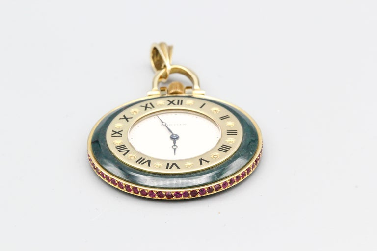 Elegant red ruby, bloodstone and 18K yellow gold pocket watch by Cartier. It features rich red rubies all around the outer diameter of the case, with bloodstone body and 18K gold accents. Quartz movement. Comes with original Cartier invoice showing