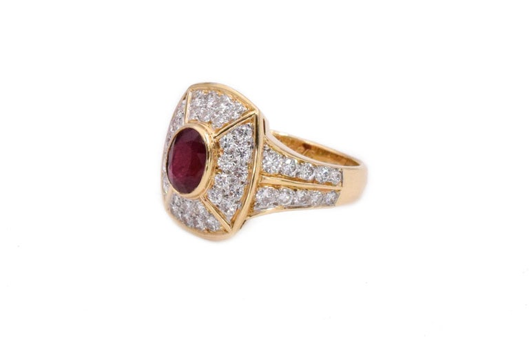 Cartier Paris ruby and diamond earrings and ring set. The set is created in a rectangular design with oval cut ruby in the center and accented by pave set diamonds. The ear clip earrings are set with two rubies oval cut rubies weighing approx. 1.6ct