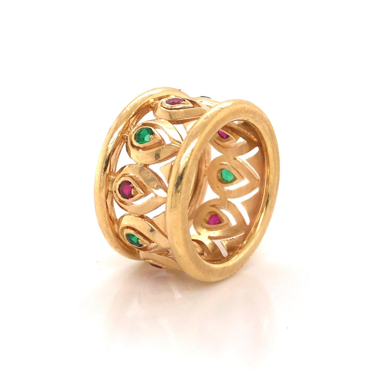 Beautiful wide band ring from Cartier. This elegant ring shows an amazing open work design crafted in 18k yellow gold. Set in a beautiful alternating pattern are natural ruby and emerald gemstones.  The workmanship on this ring is truly exceptional,