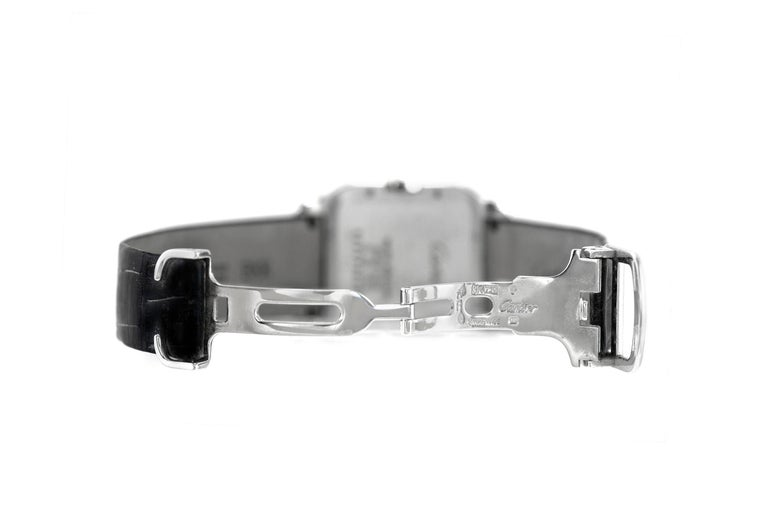 The beautiful watch is finely crafted in 18k white gold with diamonds and black leather . Signed cartier. Box + paper