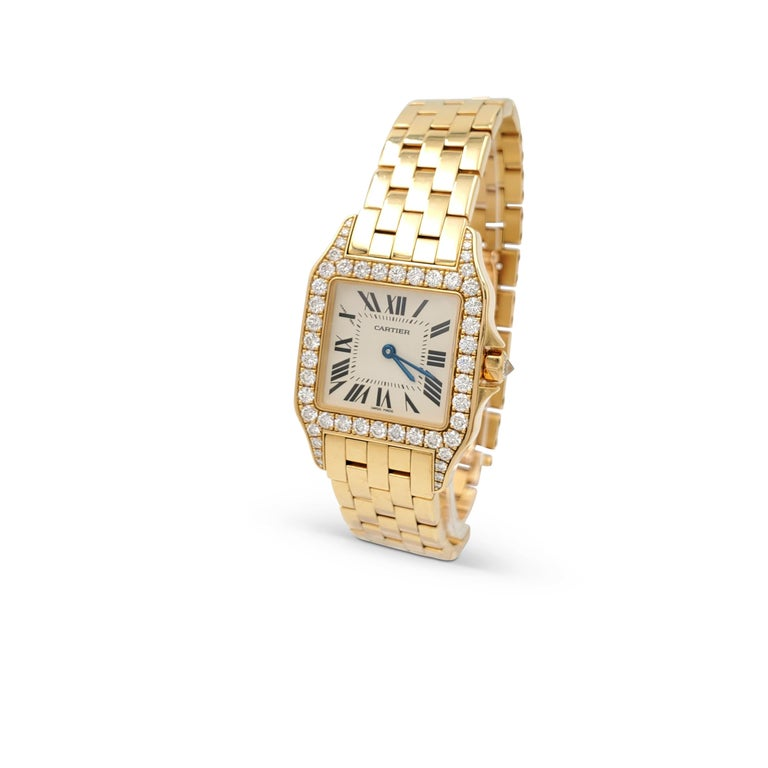 Authentic Cartier Santos Demoiselle watch crafted in 18 karat yellow gold. The octagonal case (32 mm x 26 mm) is set with an estimated 1.30 carats of high-quality round brilliant cut diamonds. Cream dial with painted black roman numerals and