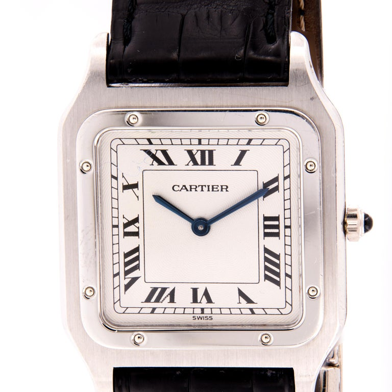 This is a pre-owned Hand-wound Cartier Santos Dumont unisex 1575 watch is in excellent condition. 27mm by 36mm case size in platinum, white roman dial on a back crocodile leather strap. This timepiece is very rare and still has the original strap