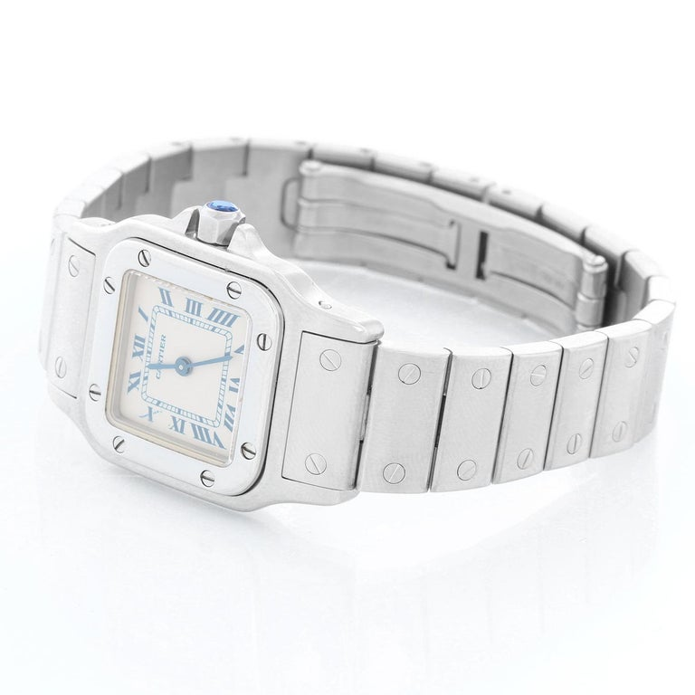 Cartier Santos Galbee Small Ladies Watch 1565 - Quartz. Stainless steel case (24mm x 35mm). Ivory dial with blue Roman numerals. Stainless steel Santos bracelet; will fit a 6 3/4 inch wrist . Pre-owned with custom box.