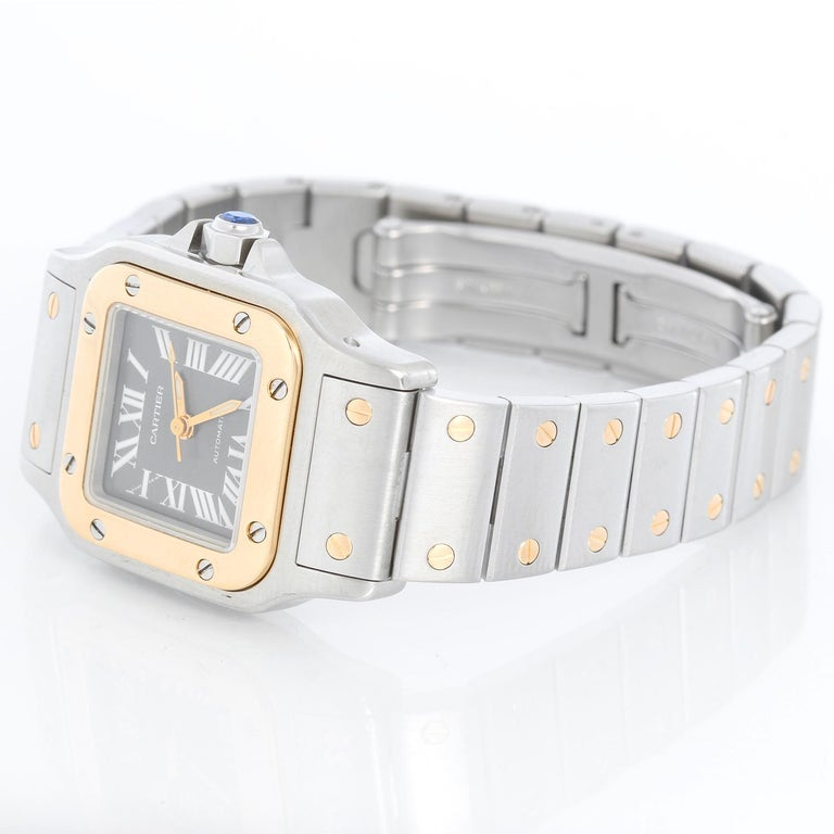 Cartier Santos Ladies 24mm Steel & Gold 2-Tone Automatic Watch 2423 - Automatic. Stainless steel case with 18k yellow gold bezel (24mm x 34mm ). Charcoal dial with luminous roman numerals. Stainless steel bracelet with gold accents. Pre-owned with