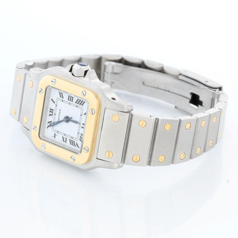 Cartier Santos Ladies 24mm Steel & Gold 2-Tone Quartz Watch 16336 - Quartz. Stainless steel case with 18k yellow gold bezel (24mm x 34mm ). Ivory dial with black roman numerals. Stainless steel bracelet with gold accents; will fit apx. 6-1/2-in.