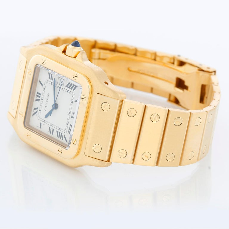 Cartier Santos Men's 18k Yellow Gold Watch W20010C5 - Automatic. 18k yellow gold case (29mm x 41mm). White dial with black Roman numerals and date at 3 o'clock. 18K Yellow Gold Santos bracelet;  will fit up to a 7 inch wrist . Pre-owned with Cartier