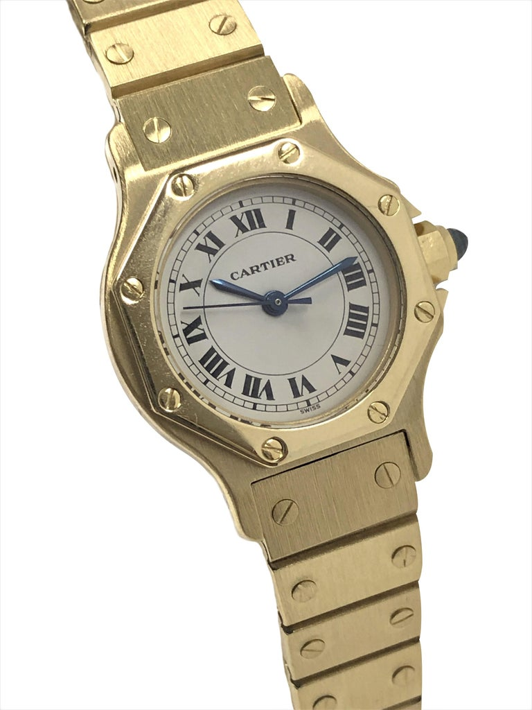 Circa 1990 Cartier Santos Collection Ladies Wrist Watch, 26 M.M. Octagon 18k Yellow Gold 2 Piece water resistant case, Automatic self winding movement, White Dial with Black Roman numerals, sweep seconds hand and a Sapphire crown. 1/2 inch wide