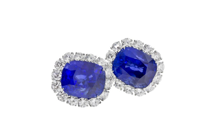 A pair of Sapphire and Diamond Earring Clips signed Cartier. Sapphires weighing respectively 25.36 and 25.39 carats set in 18.55 grams of platinum surrounded by 28 round brilliant stones weighing approximately 7 carats graded D-F VVS-VS signed
