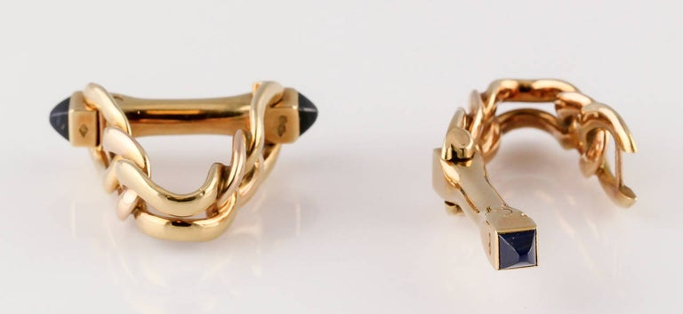 Handsome 18K yellow gold and sapphire triangle link cufflinks by Cartier, circa 1950s. They feature high quality sugarloaf cabochon sapphires on each end and feature a design which wraps around the cuff for a bold aesthetic.  Hallmarks: Cartier ,