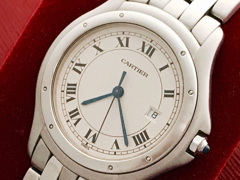 Cartier Cougar Midsize Stainless Steel Quartz Wrist Watch.  Certified pre-owned and ready to ship.  Quartz movement with date.  Stainless Steel round case (33mm dia.).  Stainless Steel Cartier bracelet with deployant clasp. Off-White Dial with black