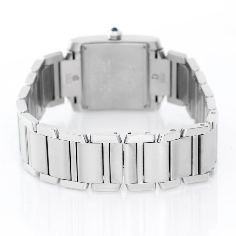 Cartier stainless steel Tank Francaise midsize wristwatch, Ref. W51011Q3, with quartz movement. Stainless steel case (25mm x 30mm). Ivory-colored dial with black Roman numerals, date at 3 o'clock. Stainless steel Cartier bracelet with deployant