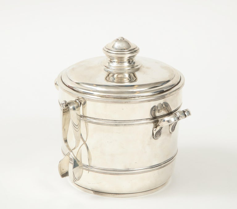 A fabulous Cartier sterling silver ice bucket with tongs with its original box. It has a perforated insulated liner that allows for moisture to escape therefore in impeccable condition.