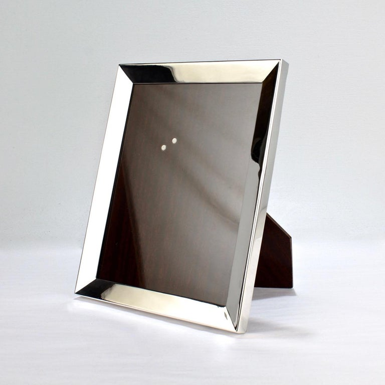 A very fine Cartier sterling silver picture or photo frame.  A perfect mantel or desk size with a handsome chamfered border.  Handmade by Eleder-Hicock & Co (formerly Lebkeucher) for the world-leading retailer Cartier. Simply the very best