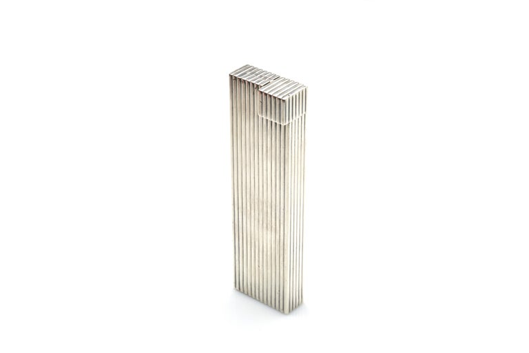 A large table lighter by Cartier, crafted out of sterling silver in a fluted pattern. This is one of the best examples of Cartier's history of supreme craftsmanship and luxury. Marked on bottom.  1930s.  Measures: 5