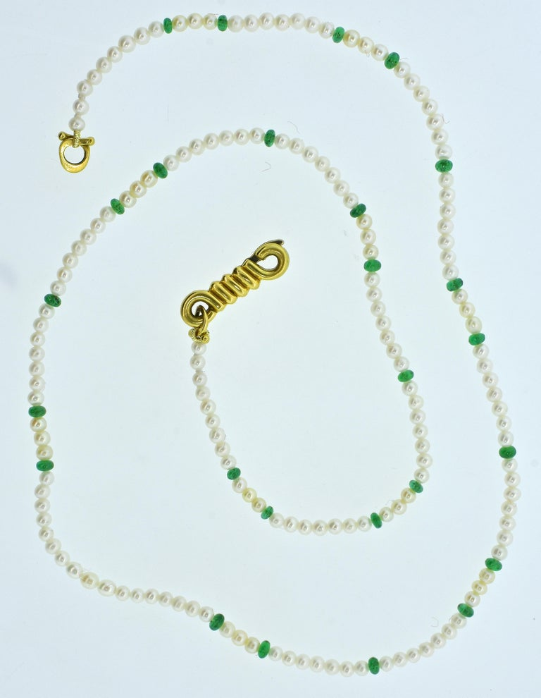 Cartier strand of small natural salt water pearls interspersed with natural emerald beads.  The 18K gold clasp is signed in block letters, Cartier and 18k.  This necklace is 20.5 inches in length, the white well matched pearls which display fine