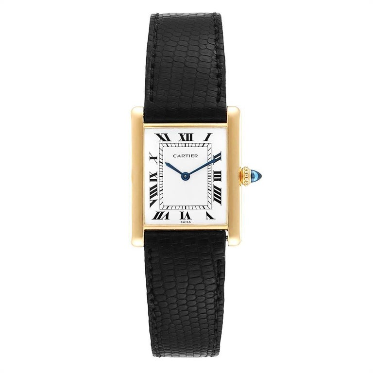 Cartier Tank Classic Paris Yellow Gold Ultra Thin Mechanical Mens Watch. Ultra thin hand made manual winding movement. 18k yellow gold case 23.0 x 30.0 mm. Circular grained crown set with the blue sapphire cabochon. 18K yellow gold bezel. mineral
