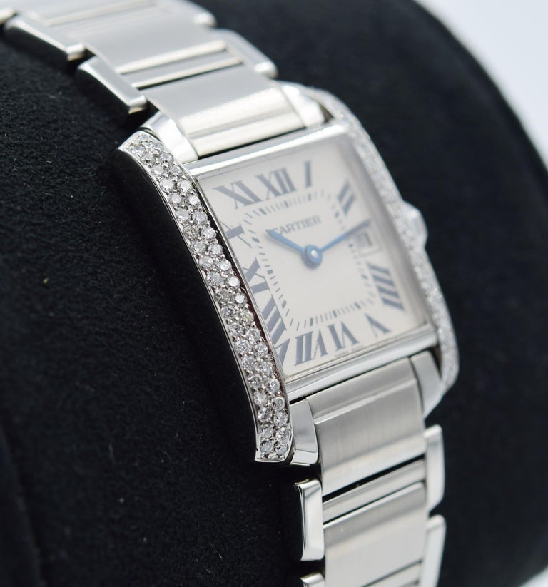 This Cartier Tank Francaise was recently traded in to our store and is in good condition with some normal indications of wear. This watch has a diamond aftermarket modification for the bezel down each side of the case. There are scratches on the